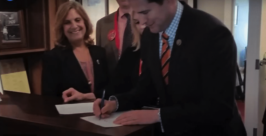 Seth Moulton, with Nancy Frates looking on, signs the first version of the ALS Disability Insurance Access Act at the May 2016 ALS Advocacy Conference